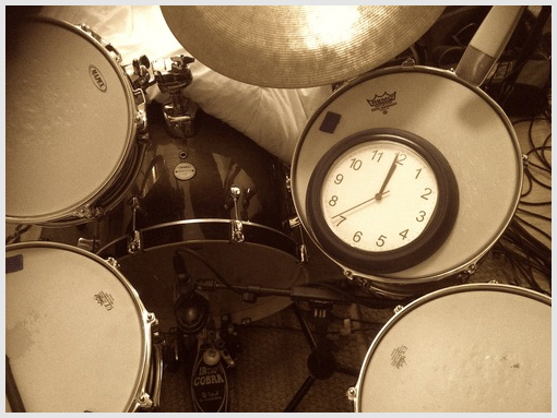 A clock showing midnight, placed on a drum kit